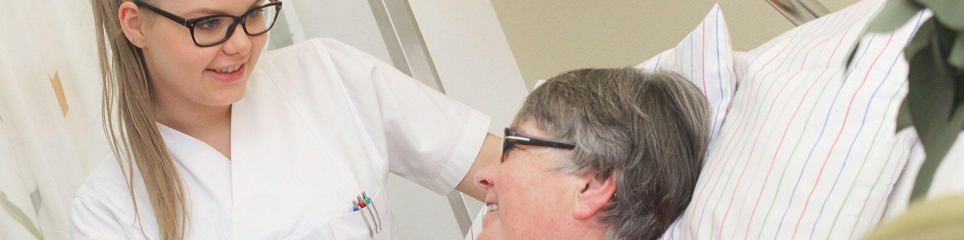 Krankenschwester schaut älterin Patientin in die Augen